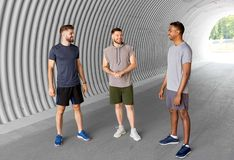 Young sporty men or male friends talking in tunnel