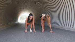 Women with fitness trackers stretching outdoors
