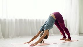 Woman does downward-facing dog pose at yoga studio