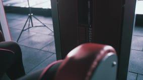Fitness, sport, het bodybuilding, het uitoefenen en mensenconcept - de jonge spieren van de vrouwenverbuiging op been drukken mac stock footage