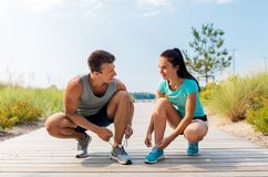 Couple of joggers tying sneakers shoelaces Royalty Free Stock Photo