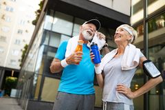 Fitness, sport and lifestyle concept - happy mature couple in sports clothes outdoors royalty free stock images