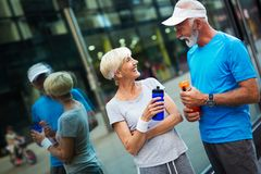 Fitness, sport and lifestyle concept - happy mature couple in sports clothes outdoors stock image