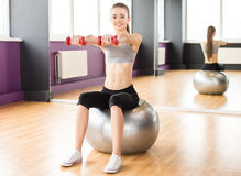 Fitness. Sport, fitness, lifestyle concept. Smiling woman with exercise ball and dumbbells in gym is looking at the camera Royalty Free Stock Photo