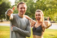 Fitness sport loving couple showing thumbs up gesture looking camera. Image of happy fitness sport loving couple friends in park outdoors showing thumbs up royalty free stock photo