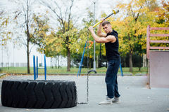 Fitness sport man workout outdoor. with hammer and tractor tire. royalty free stock photography