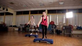 Fitness, sport, opleiding, aerobics en mensenconcept - groep die mensen met steppers in gymnastiek uitwerken stock footage