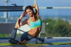 Fitness, sport, opleiding en levensstijl concept - het glimlachen vrouw het uitrekken zich op mat in gymnastiek licht van een gro royalty-vrije stock foto