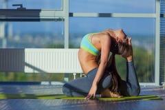Fitness, sport, opleiding en levensstijl concept - het glimlachen vrouw het uitrekken zich op mat in gymnastiek licht van een gro stock foto's