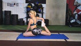 Fitness, sport, opleiding en levensstijl concept - het glimlachen vrouw het uitrekken zich been op mat in gymnastiek stock footage
