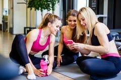 Fitness, sport, opleiding, gymnastiek en levensstijlconcept - groep gelukkige vrouwen met flessen en smartphone in gymnastiek royalty-vrije stock foto's