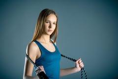 Fitness, sport, opleiding, mensen en levensstijlconcept - jonge vrouw of tiener die oefeningen met expander of weerstandsband doe stock afbeelding