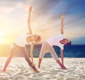 Couple making yoga exercises on beach Stock Image