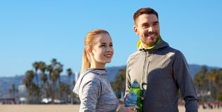 Couple of sportsmen with water over venice beach Royalty Free Stock Photography