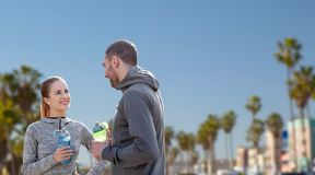 Couple of sportsmen with water over venice beach Royalty Free Stock Photo
