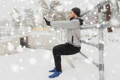 Sports man doing squats at fence in winter Royalty Free Stock Photography