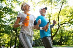 Fitness, sport, people, exercising and lifestyle concept - senior couple running. Fitness, sport, people, exercising and lifestyle concept - mature couple stock photo