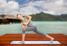 Woman making yoga low angle lunge pose outdoors. Fitness, sport, people and healthy lifestyle concept - woman making yoga low angle lunge pose on wooden pier royalty free stock photography