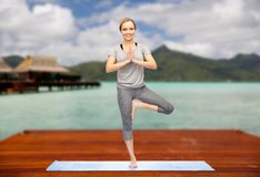 Woman making yoga in tree pose outdoors. Fitness, sport, people and healthy lifestyle concept - woman making yoga in tree pose on wooden pier over island beach Stock Image