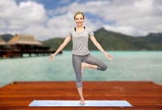 Woman making yoga in tree pose on mat outdoors. Fitness, sport, people and healthy lifestyle concept - woman making yoga in tree pose on wooden pier over island Stock Photo