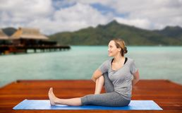 Woman making yoga in twist pose on mat outdoors. Fitness, sport, people and healthy lifestyle concept - woman making yoga in twist pose on wooden pier over Stock Photos