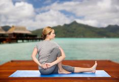 Woman making yoga in twist pose on mat outdoors. Fitness, sport, people and healthy lifestyle concept - woman making yoga in twist pose on wooden pier over Stock Image