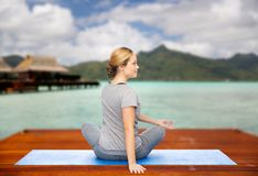 Woman making yoga in twist pose on mat outdoors. Fitness, sport, people and healthy lifestyle concept - woman making yoga in twist pose on wooden pier over Stock Images