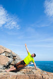 Fitness, sport, people and lifestyle concept - young man making yoga exercises on beach from back. Man running on a rural road during sunset in the mountains Royalty Free Stock Photo