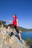 Fitness, sport, people and lifestyle concept - young man making yoga exercises on beach from back. Man running on a rural road during sunset in the mountains Stock Photography