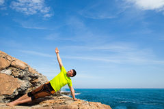 Fitness, sport, people and lifestyle concept - young man making yoga exercises on beach from back. Man running on a rural road during sunset in the mountains Royalty Free Stock Images