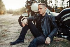 Handsome rider guy in black biker jacket on classic style cafe racer motorcycle at sunset. royalty free stock photo