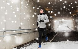 Happy man running along subway tunnel in winter. Fitness, sport, people, season and healthy lifestyle concept - happy young man running along pedestrian subway Stock Photography