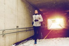 Happy man running along subway tunnel in winter. Fitness, sport, people, season and healthy lifestyle concept - happy young man running along pedestrian subway Royalty Free Stock Photos