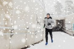 Man running out of subway tunnel in winter. Fitness, sport, people, season and healthy lifestyle concept - young man running out of pedestrian subway tunnel in Royalty Free Stock Images