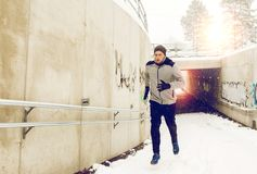 Man running out of subway tunnel in winter. Fitness, sport, people, season and healthy lifestyle concept - young man running out of pedestrian subway tunnel in Royalty Free Stock Photos