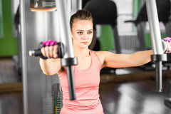 Fitness, sport, power-lifting and people concept - sporty girl building some muscles on a simulator. Fitness, sport, power-lifting and people concept - a sporty Royalty Free Stock Images