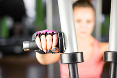 Fitness, sport, power-lifting and people concept - sporty girl building some muscles on a simulator. Fitness, sport, power-lifting and people concept - a sporty Stock Photo