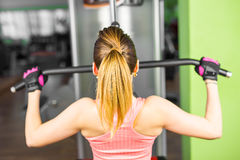 Fitness, sport, power-lifting and people concept - sporty girl building some muscles on a simulator. Fitness, sport, power-lifting and people concept - a sporty Royalty Free Stock Image