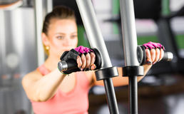 Fitness, sport, power-lifting and people concept - sporty girl building some muscles on a simulator. Fitness, sport, power-lifting and people concept - sporty Royalty Free Stock Image