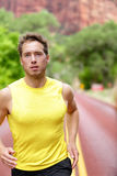Fitness sport runner man running determined. And focused with concentration training for success and health. Male athlete in sprint run in workout for marathon Stock Photos