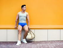 Fitness, sport, sportswear concept - sportsman with bag over colorful orange wall background in a city looking in profile royalty free stock photos