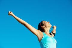 Fitness and sport success. Successful happy fitness woman raising arms to the sky after sport achievement outdoor. Sporty girl enjoying freedom Stock Photography