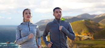 Couple with earphones running over big sur coast Royalty Free Stock Photo