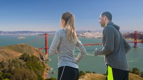 Couple with earphones running over san francisco Royalty Free Stock Image