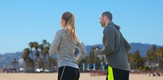 Couple with earphones running over venice beach Royalty Free Stock Photography