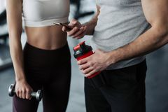 Fitness, sport, technology and slimming concept - close up of smiling young woman and personal trainer with smartphone and water royalty free stock photos