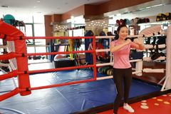 Asain chinese smiling girl boxing in the gym. Sports, power. Fitness, sport, training, gym and lifestyle concept - A shot of an asian female punching Royalty Free Stock Images