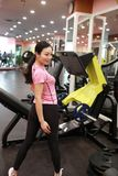 Asain chinese smiling people exercising in the gym. Sports, power. Fitness, sport, training, gym and lifestyle concept -  smiling woman exercising in the gym Royalty Free Stock Image