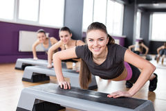 Fitness. Sport, training, gym and lifestyle concept. Three young women are working out with steppers in gym
