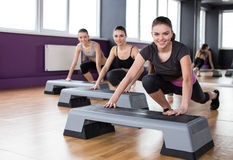 Fitness. Sport, training, gym and lifestyle concept. Three young women are working out with steppers in gym Royalty Free Stock Photo